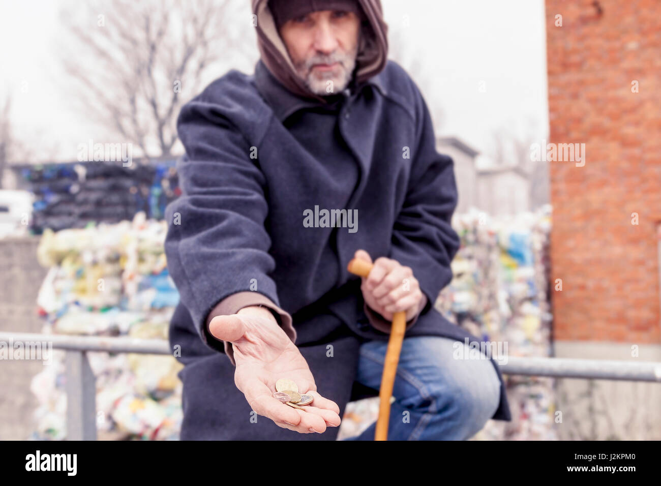 homeless asks charity in landfill - Stock Image
