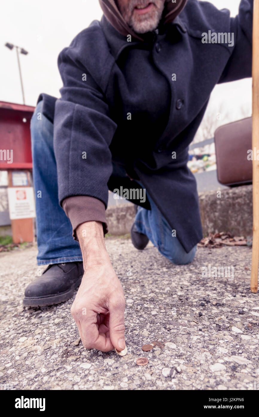 homeless collects coins in landfill - Stock Image
