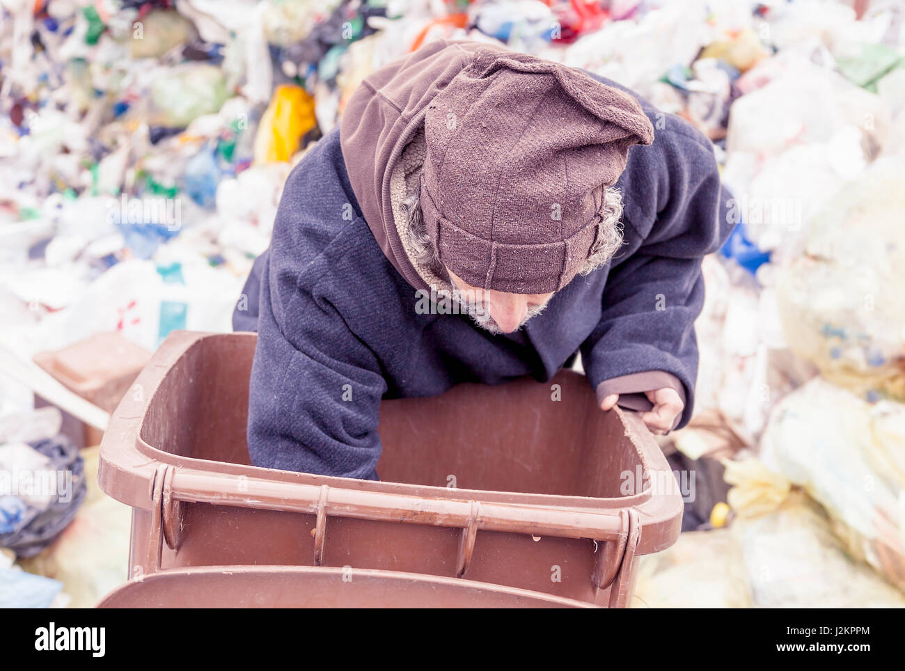 homeless rummages in the dustbin of landfill - Stock Image