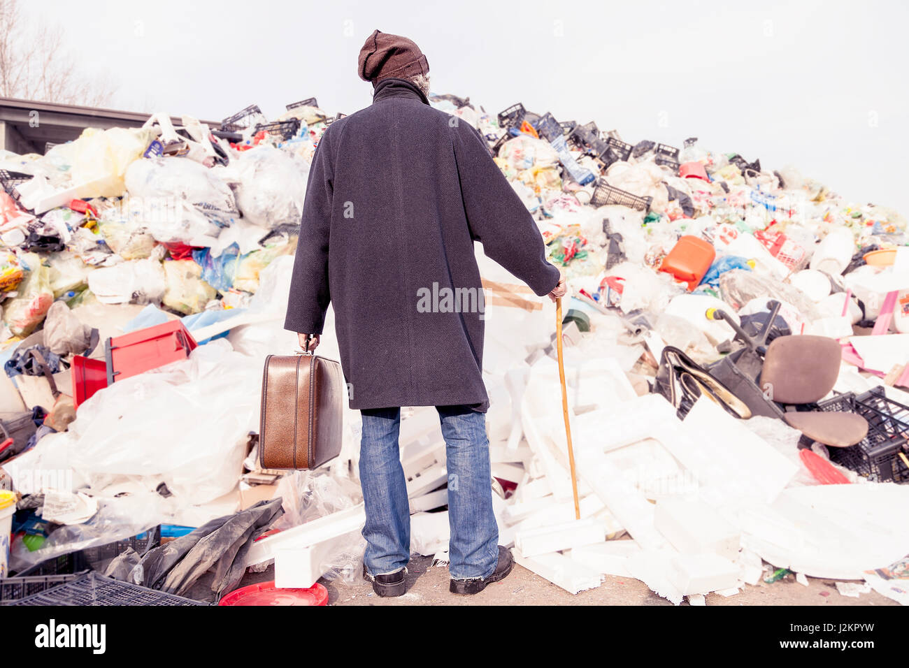 homeless standing in front of a plastic mountain - Stock Image