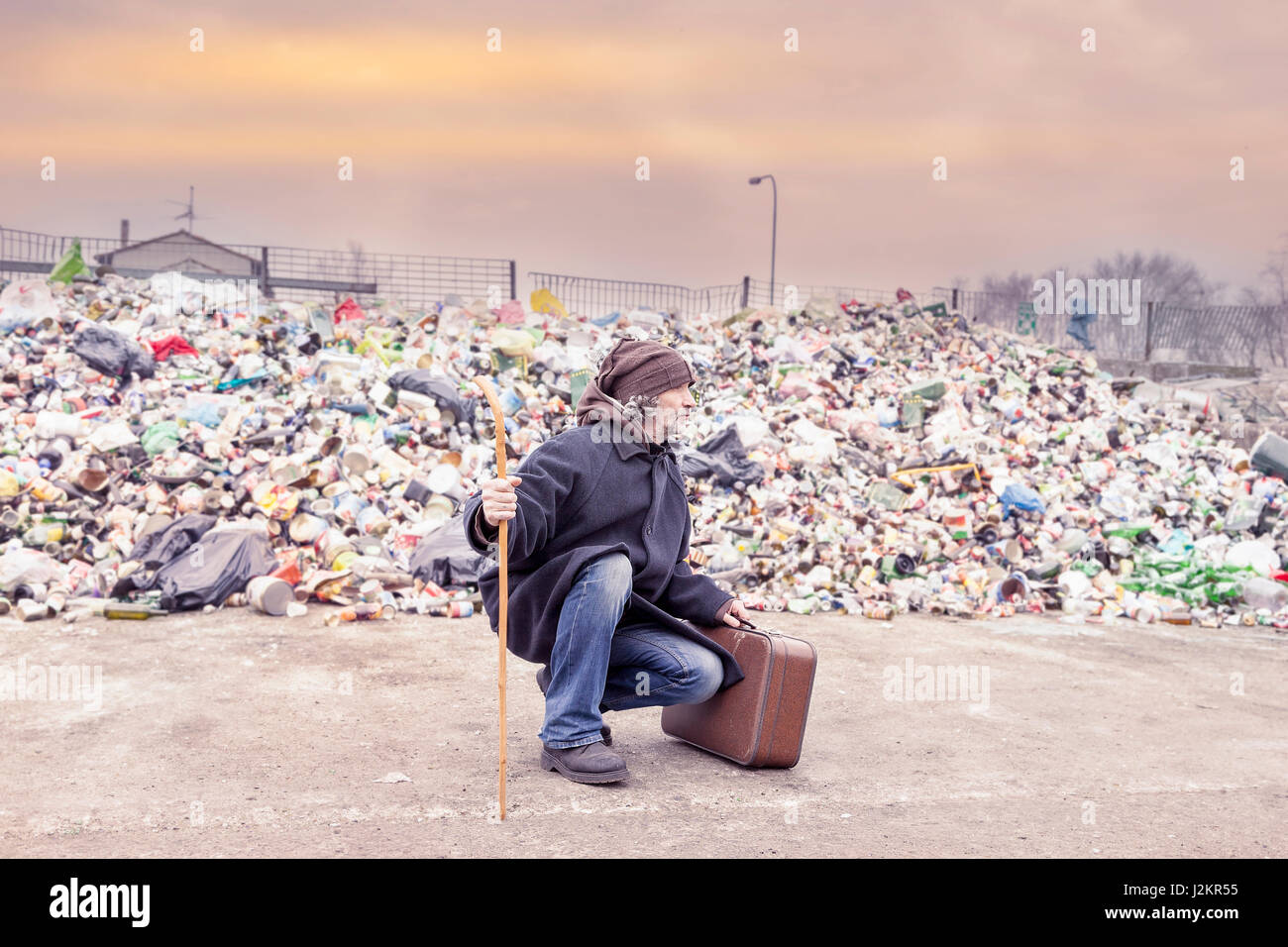 homeless with suitcase lives in landfill - Stock Image