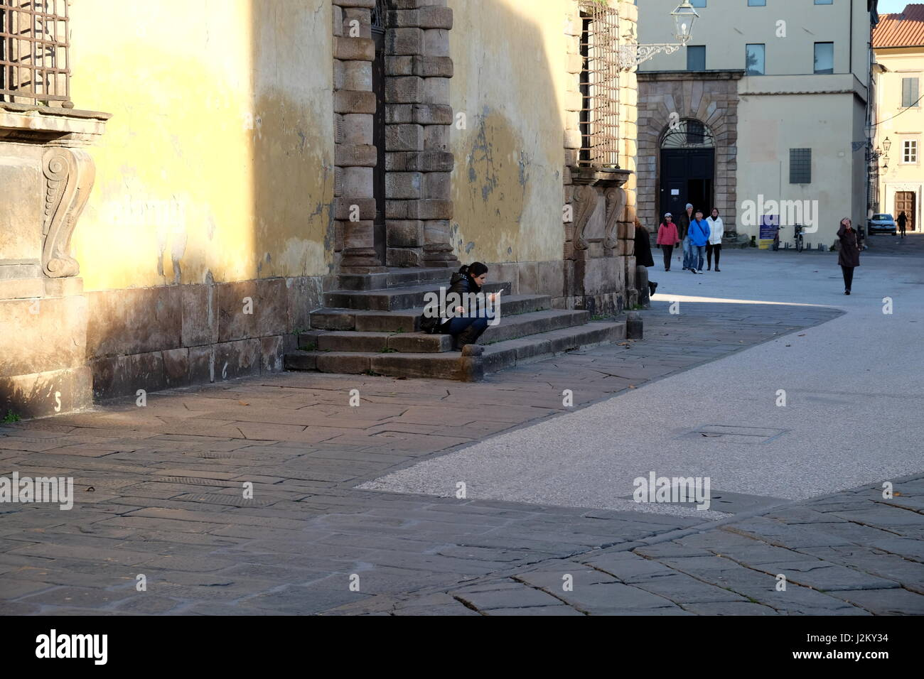 Girl (young woman) texting on smartphone in the street - Spontaneous unposed photography, central Lucca, Tuscany, - Stock Image
