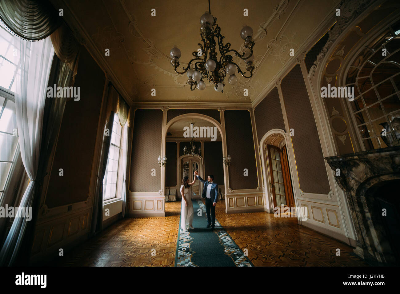 Beautiful Newlywed Couple Dancing In Vintage Victorian House Interior With  Antique Luster, Wooden Panels And