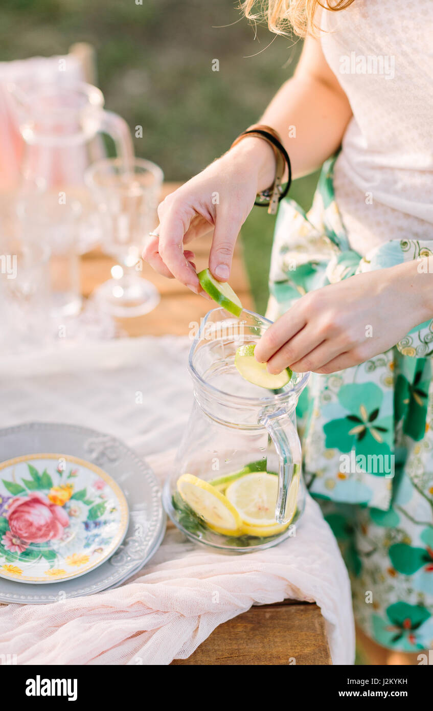 picnic, people, food, summer, holiday concept - cocktail lemonade non-alcoholic, hands of young woman mix slices Stock Photo