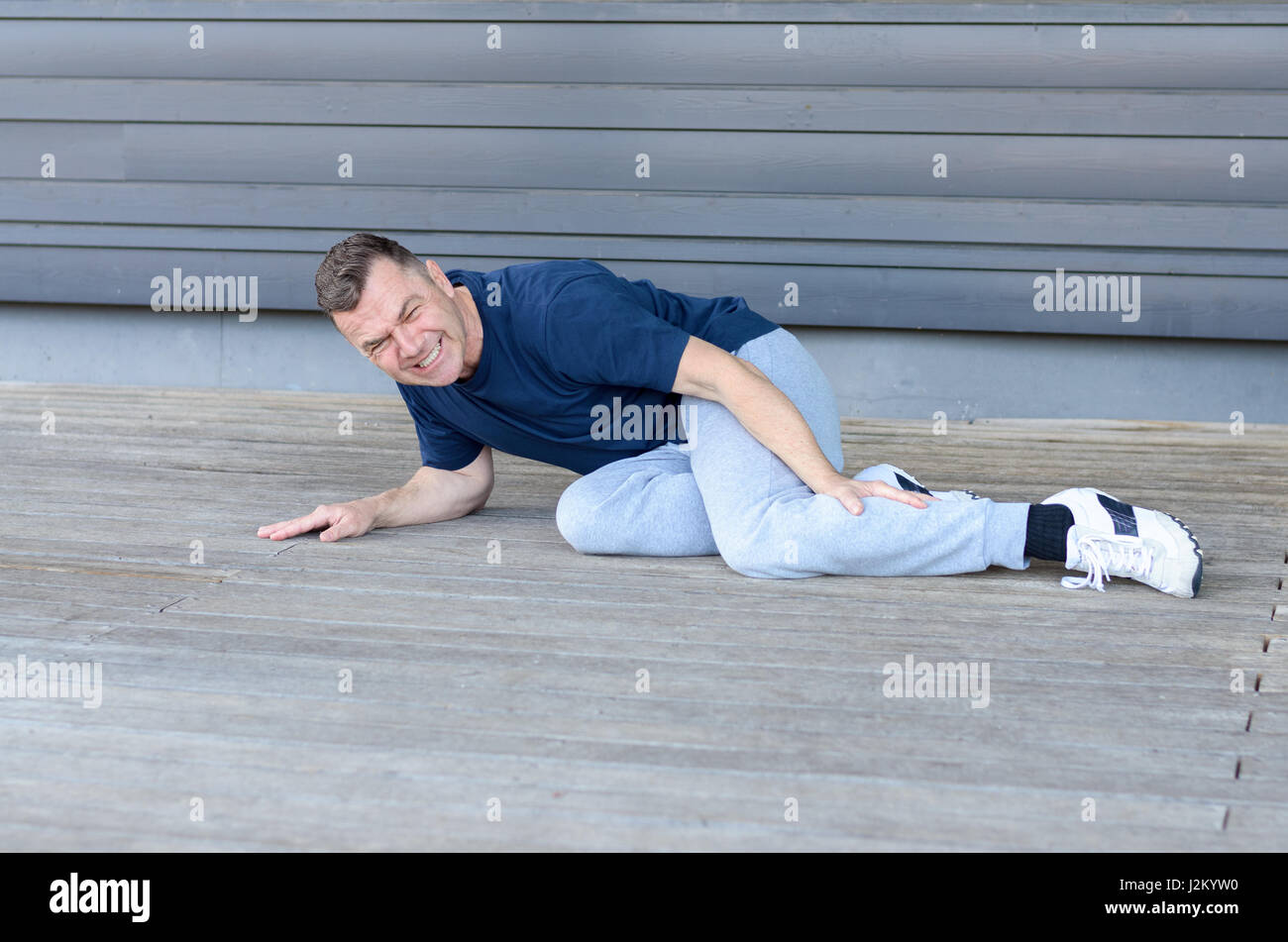 Sporty middle-aged man with muscle cramps in his calf lying on the floor clutching his leg and grimacing in pain - Stock Image