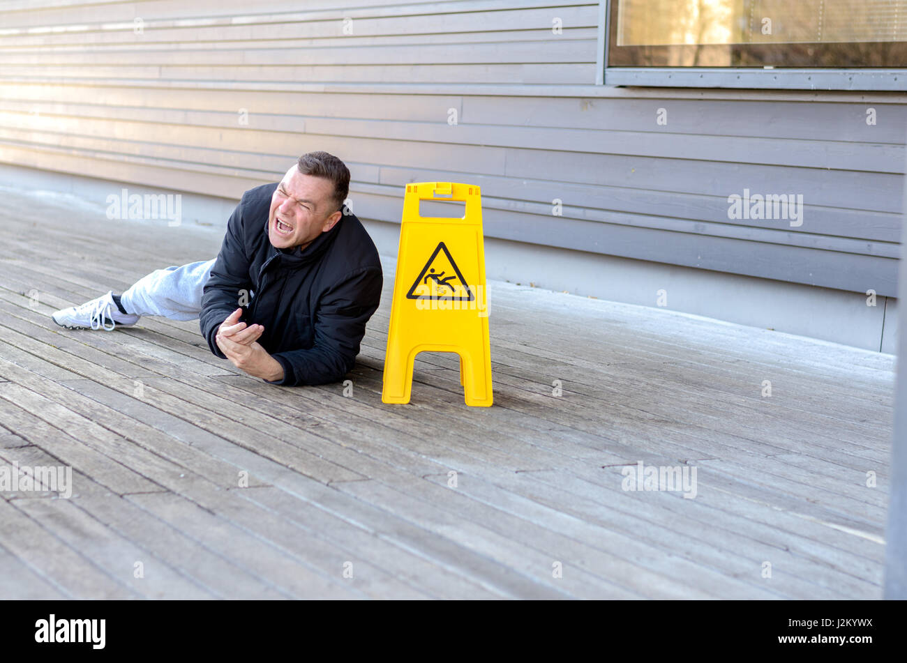 Middle-aged man taken a fall on a slippery floor right alongside a portable yellow warning sign grimacing in pain - Stock Image