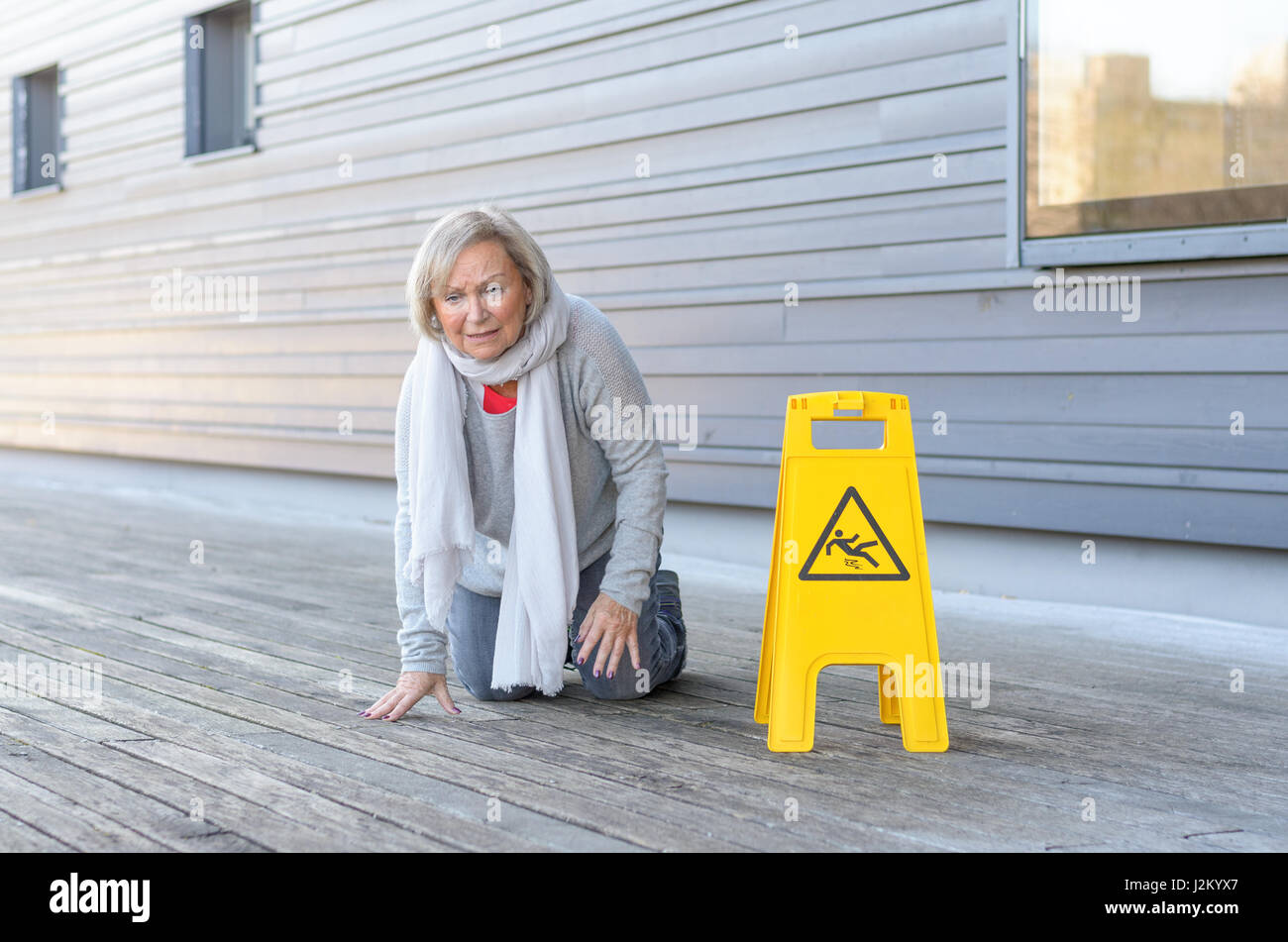 Elderly woman crawling on her knees and grimacing in pain after slipping and falling on a wet wooden deck alongside - Stock Image