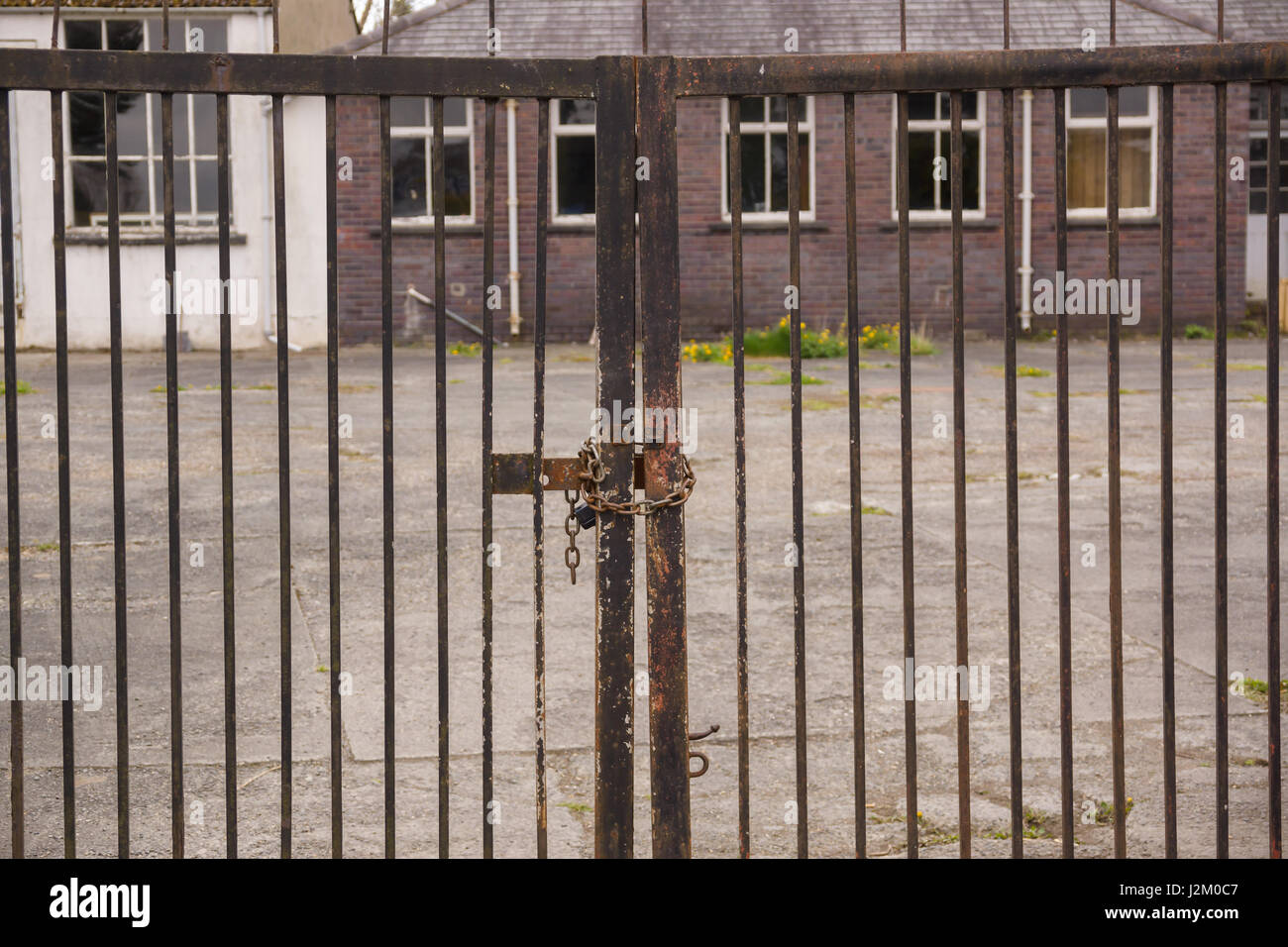 Set of locked security gates at a derelict or abandoned industrial or commercial premises - Stock Image