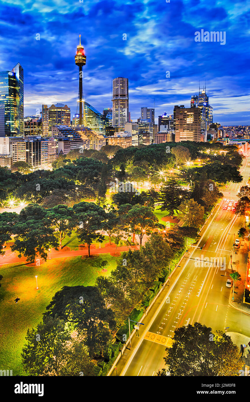 Sydney hyde park and CBD towers at sunset from elevated position. Illuminated city architecture and street roads - Stock Image
