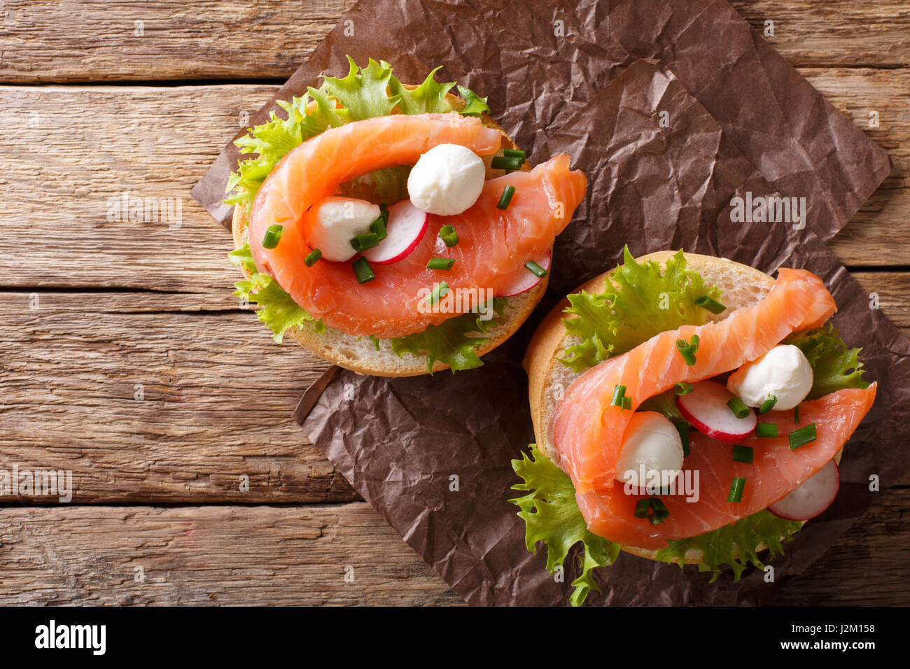 Sandwiches with salted salmon, mozzarella, frisee, onion and radish close-up on the table. horizontal view from - Stock Image