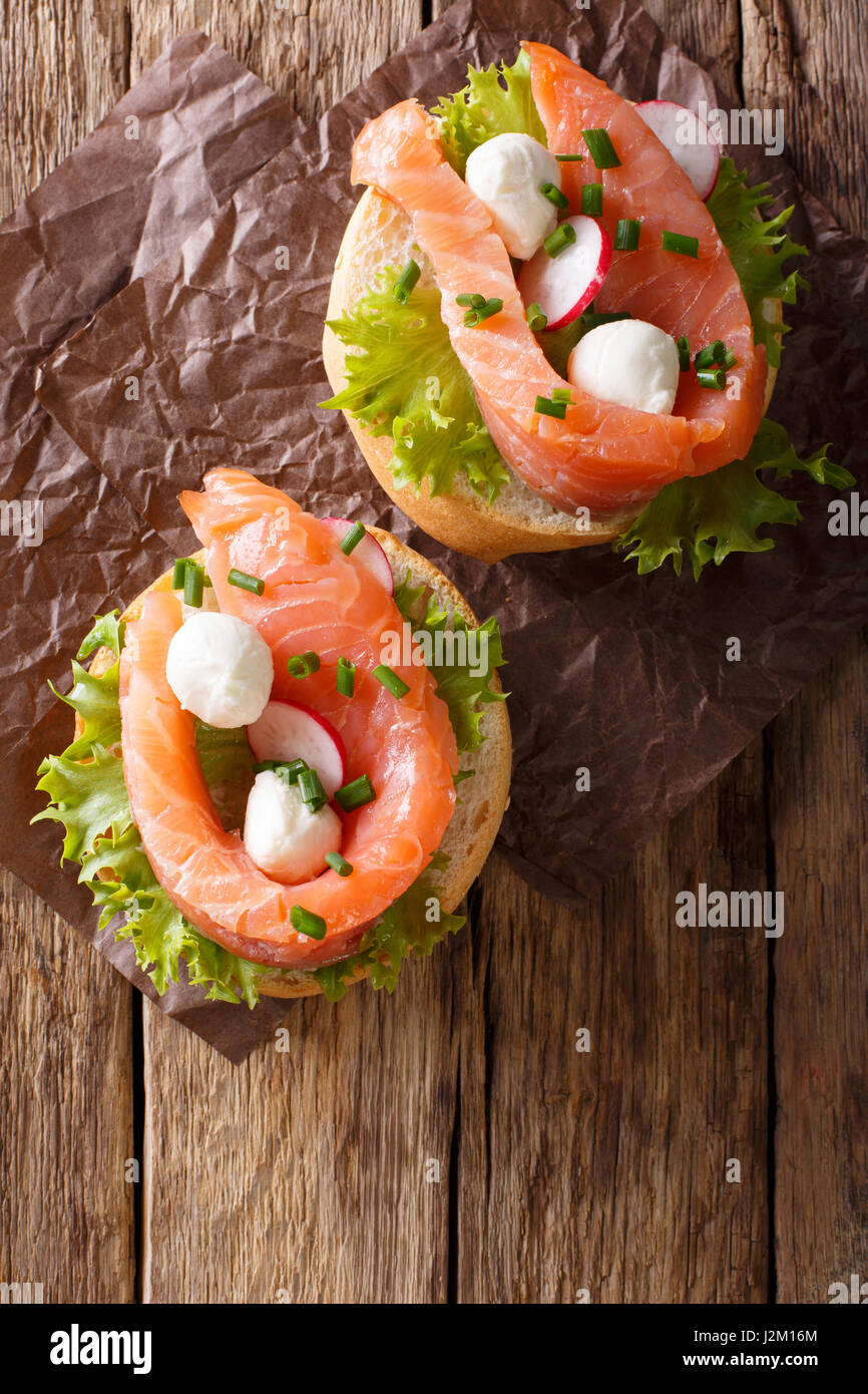 Sandwiches with salted salmon, mozzarella, frisee, onion and radish close-up on the table. Vertical view from above - Stock Image