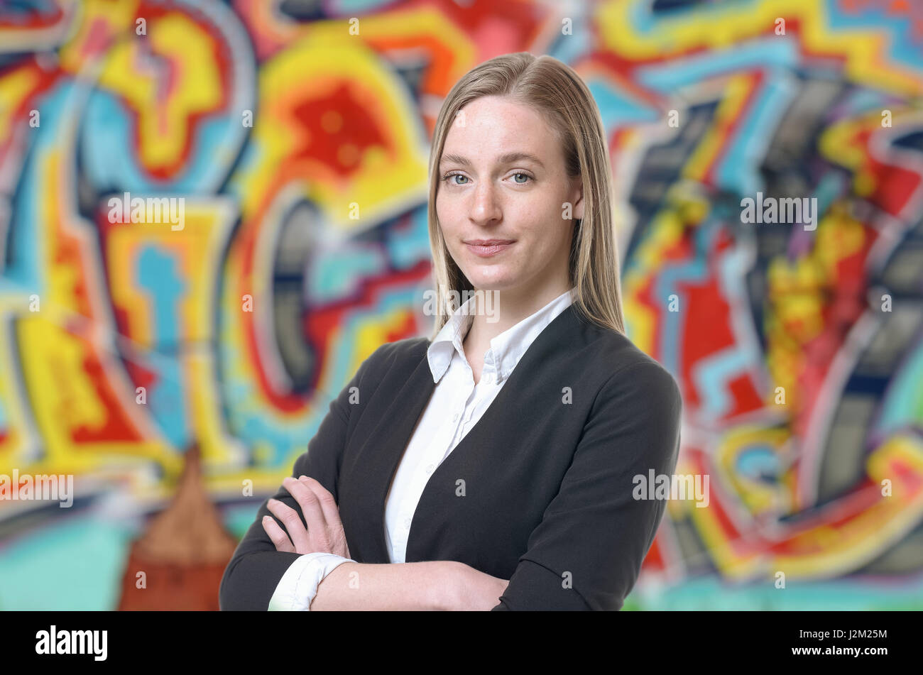 Confident grinning blond woman in sweater and white shirt with folded arms. Colorful graffiti art in background. - Stock Image