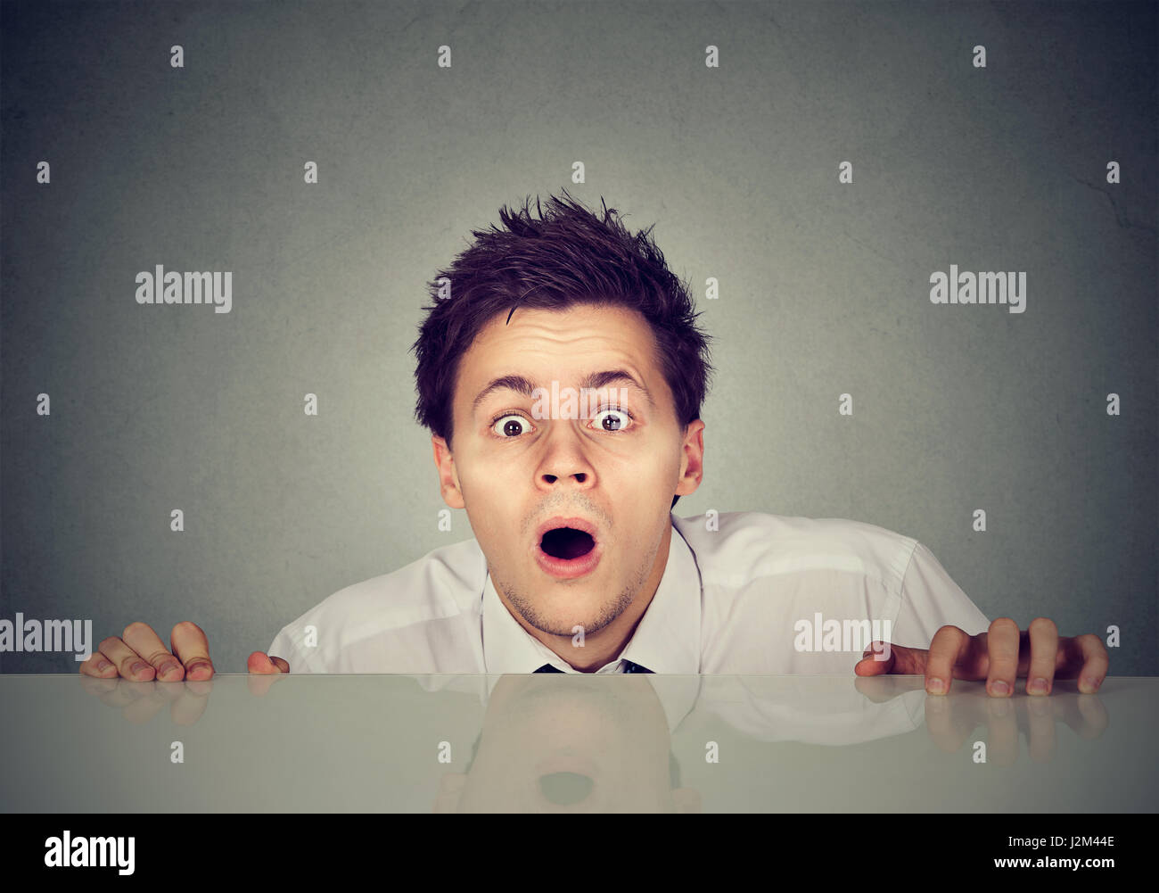 worried young man looks at camera - Stock Image