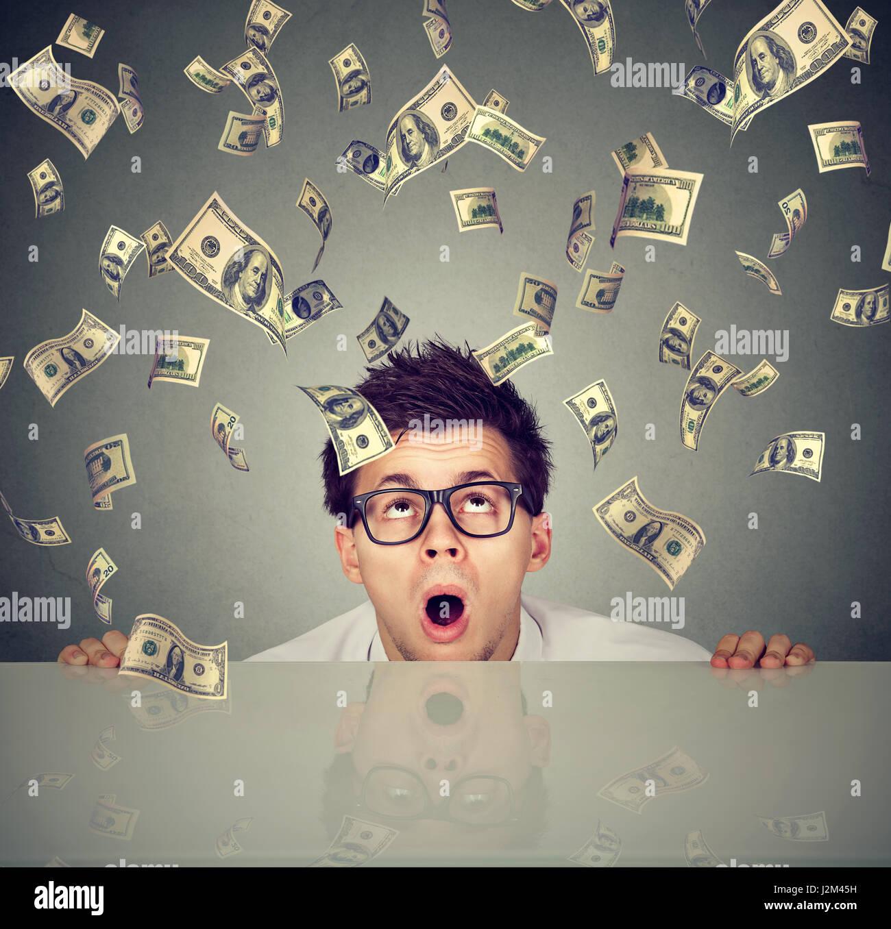 Surprised man under money rain peeking from under the table - Stock Image