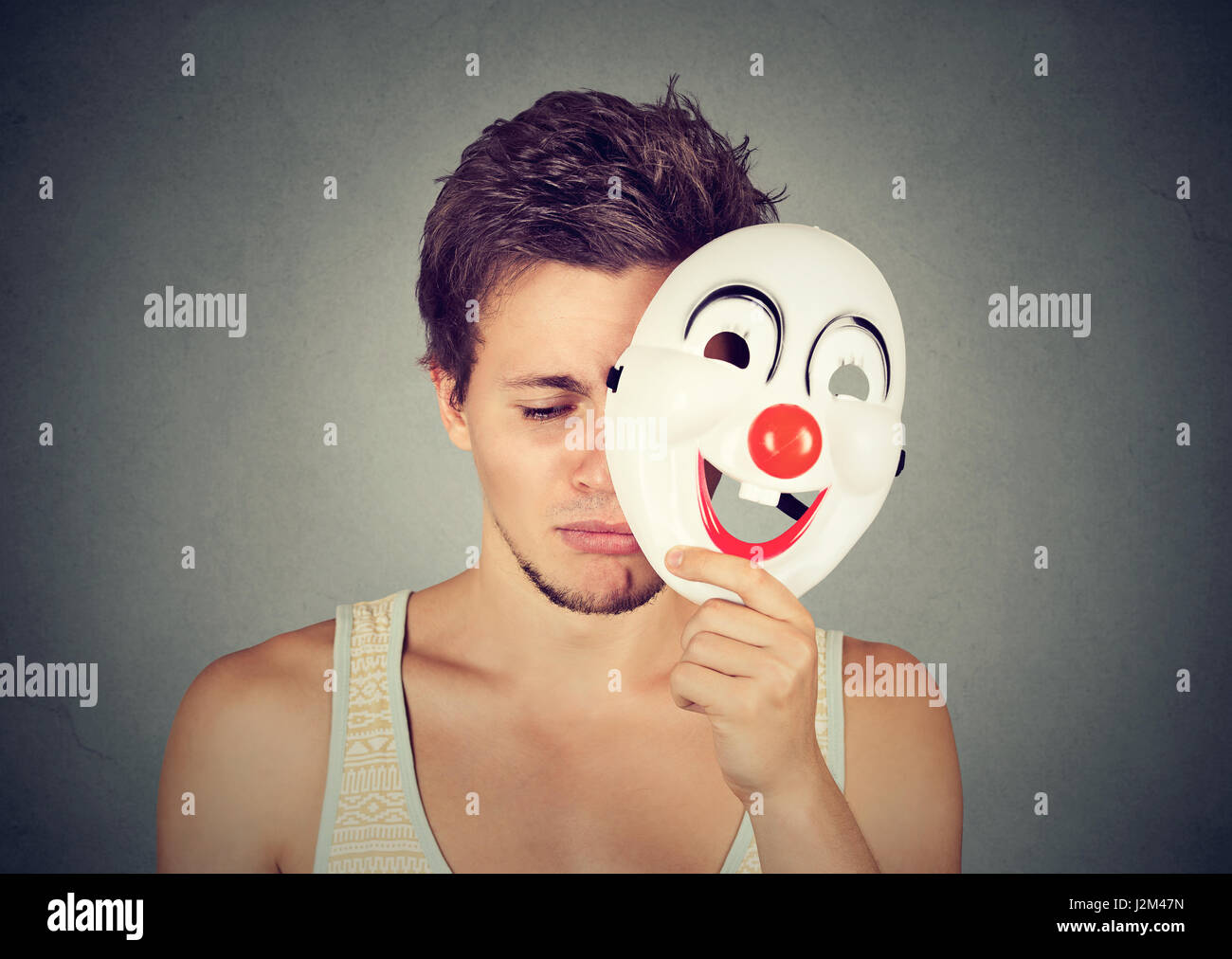 Young sad man taking off clown mask isolated on gray wall background. Human emotions - Stock Image