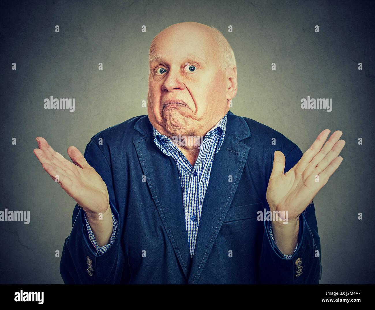 Senior confused man is shrugging his shoulders Stock Photo