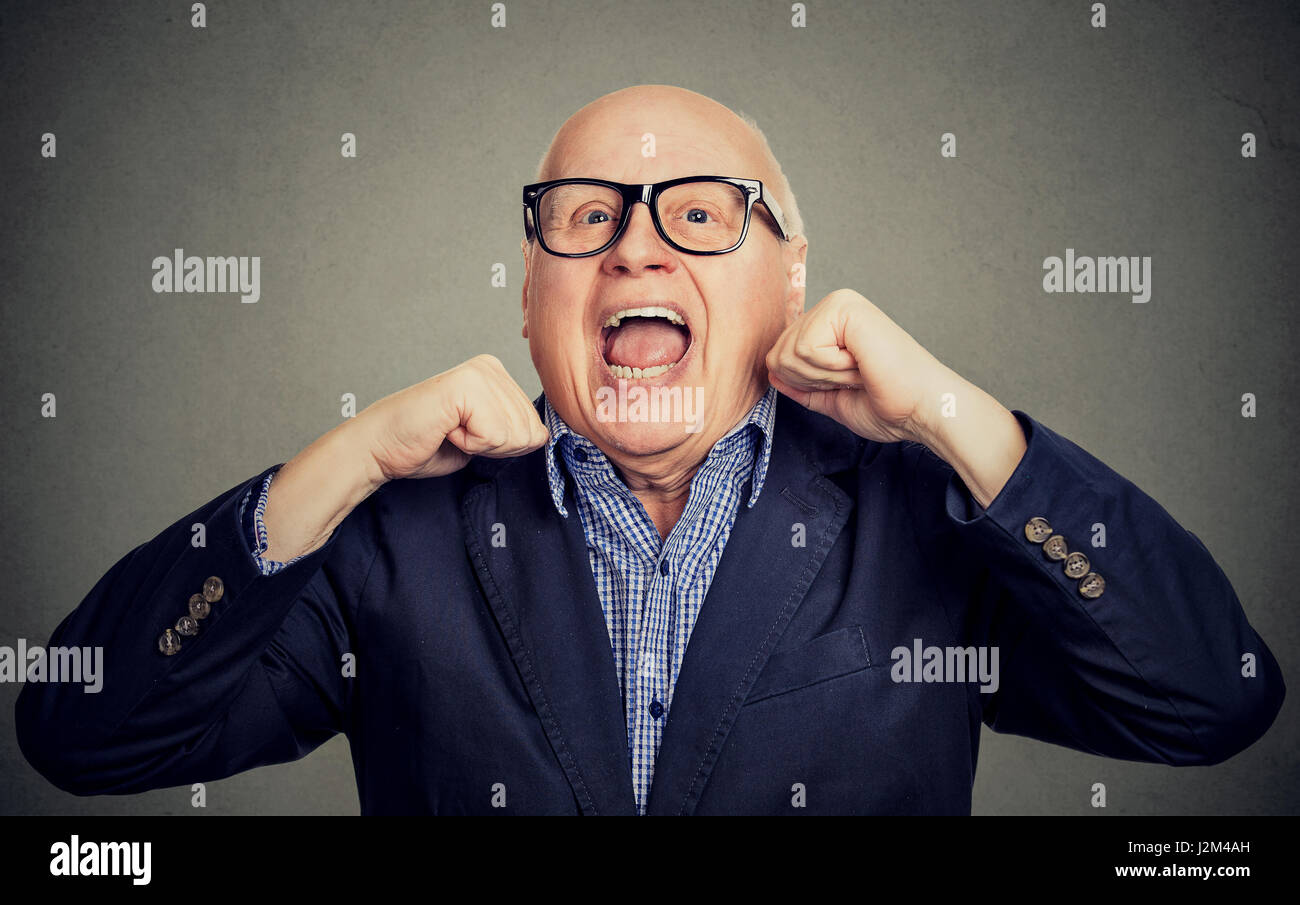 Portrait of happy laughing senior old man with hands up isolated on gray background - Stock Image