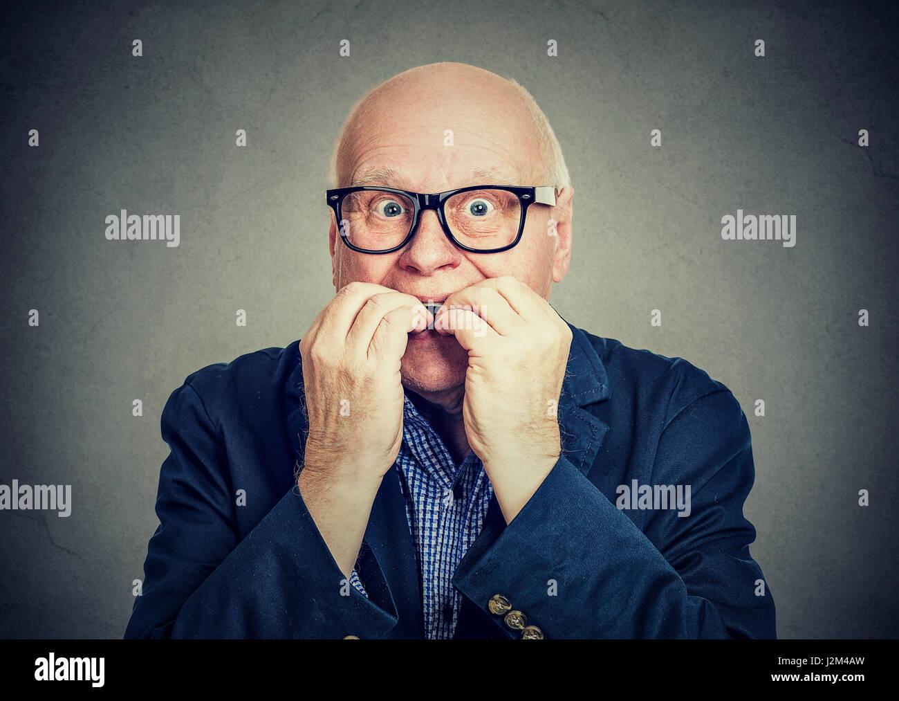 Anxious scared senior man biting fingernails - Stock Image