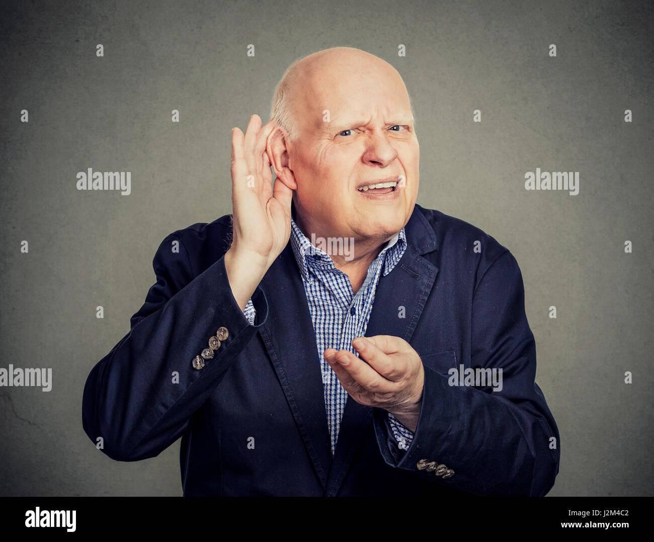 Senior man, hard of hearing, placing hand on ear asking someone to speak up - Stock Image