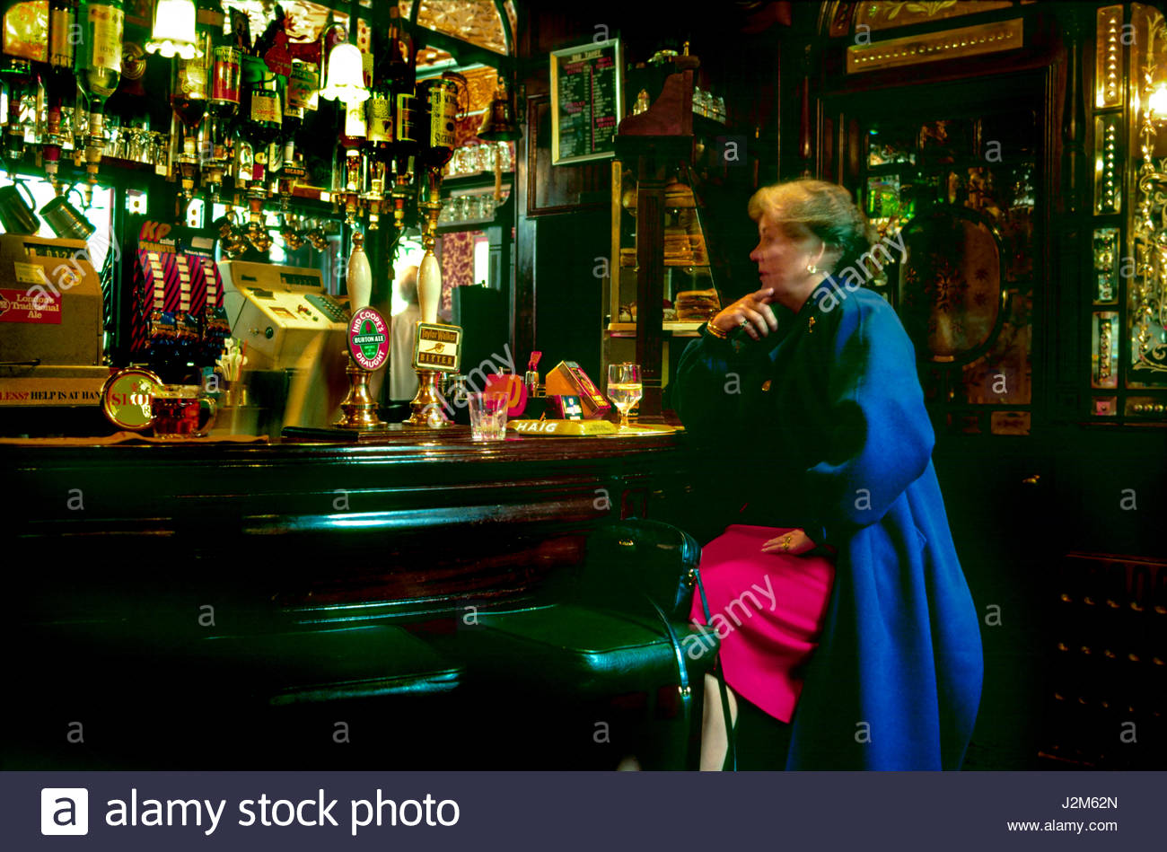 Duke of York, St. James's, London, England, United Kingdom. Woman sitting at bar counter in the Red Lion Pub. - Stock Image