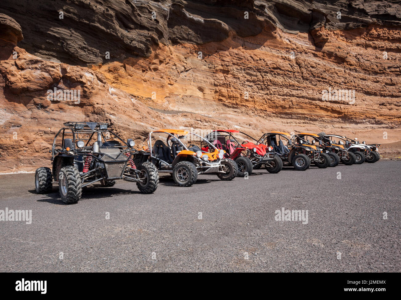 Buggies in front of a wall of rock - Stock Image