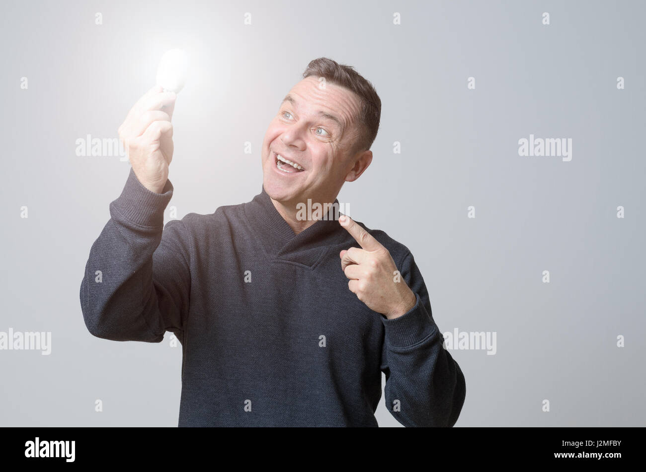 Motivated middle-aged man holding a brightly glowing light bulb with a look of gleeful wonderment conceptual of - Stock Image