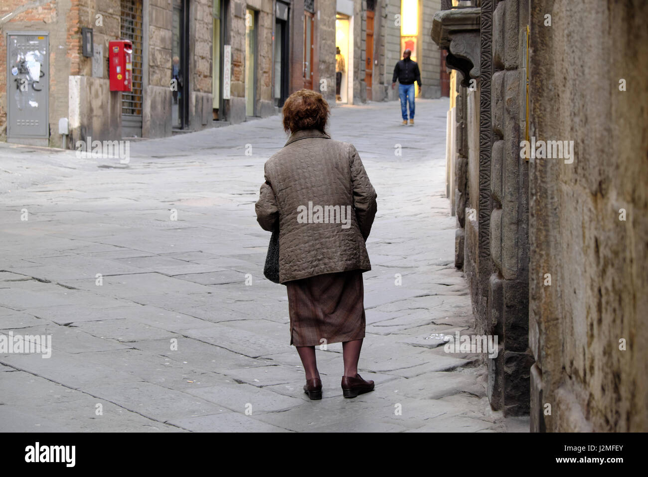Old Italian woman from behind struggling with walking - Sunday stroll - Fit black man wearing jeans and dark jacket - Stock Image