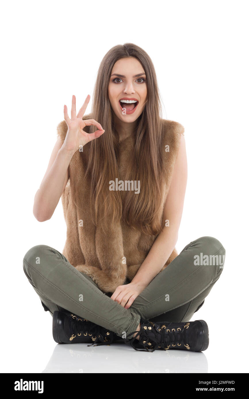 Beautiful young woman in brown fur waistcoat and khaki pants sitting on floor with legs crossed, shouting and showing - Stock Image