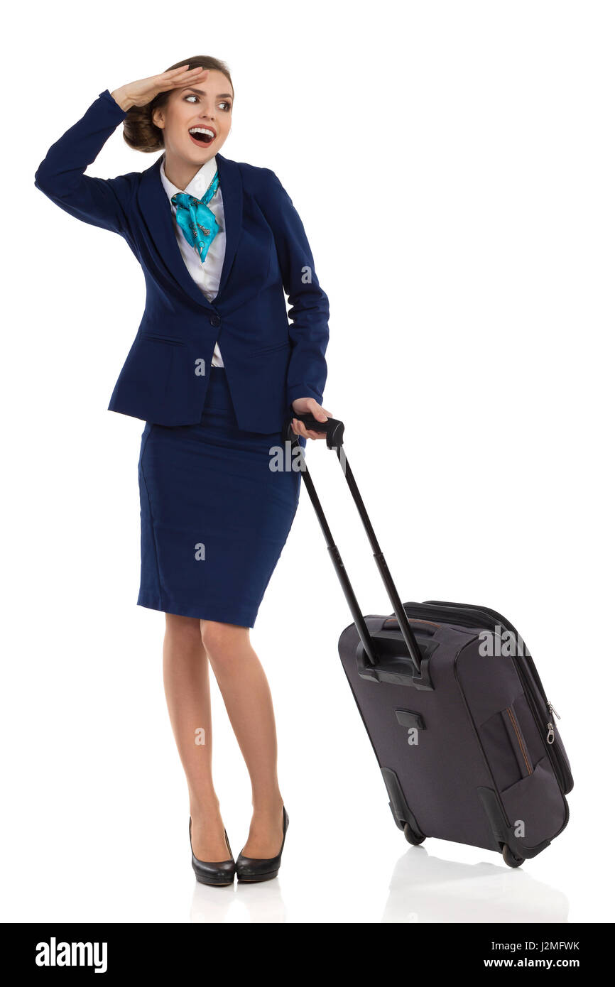 Smiling woman in blue suit and skirt standing with trolley bag, showing, saluting and looking away. Full length - Stock Image