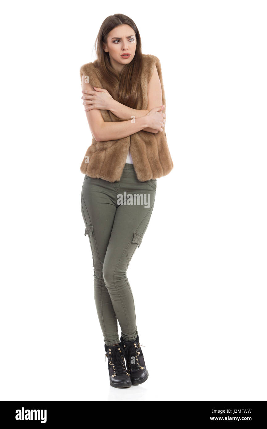 Young woman in brown fur waistcoat, khaki pants and black boots standing, hugging herself and looking away. Full - Stock Image
