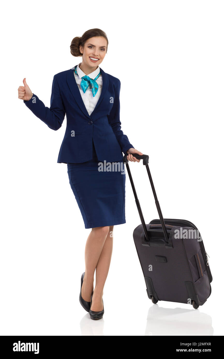 Smiling woman in blue suit and skirt standing with trolley bag, showing thumb up and looking at camera. Full length - Stock Image