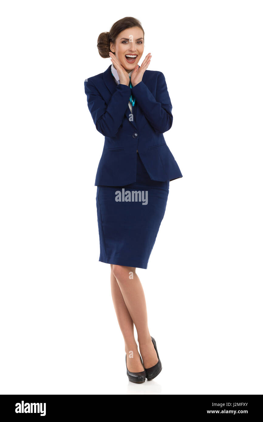 Young woman in blue formalwear and high heels, standing with head in hands and shouting. Front view. Full length - Stock Image