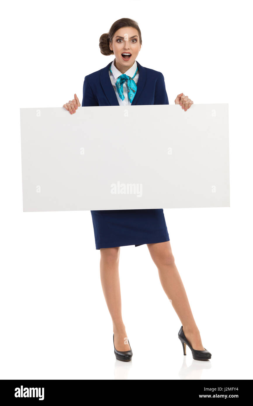 Surprised young woman in blue formalwear and high heels, holding blank placard. Front view. Full length studio shot - Stock Image