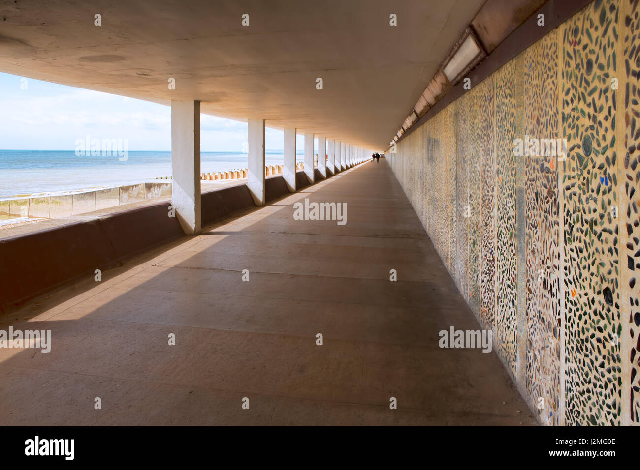 A beach-front covered concrete walkway with mosaic-pattern wall, sea view to one side and strong leading lines away - Stock Image
