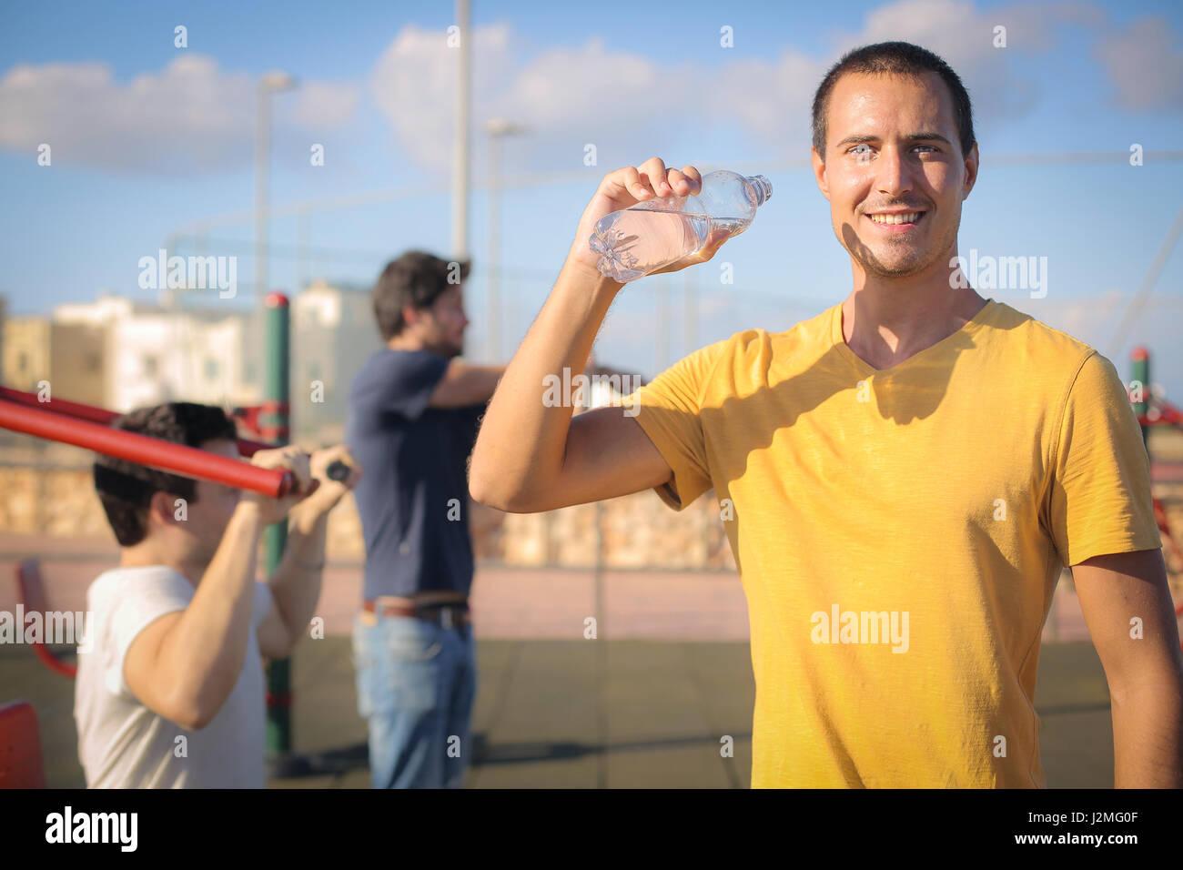 3 men street workouting and drinking water - Stock Image