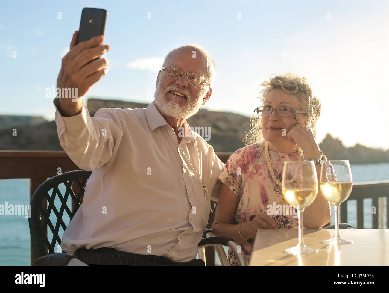 Old couple taking a selfie outside Stock Photo