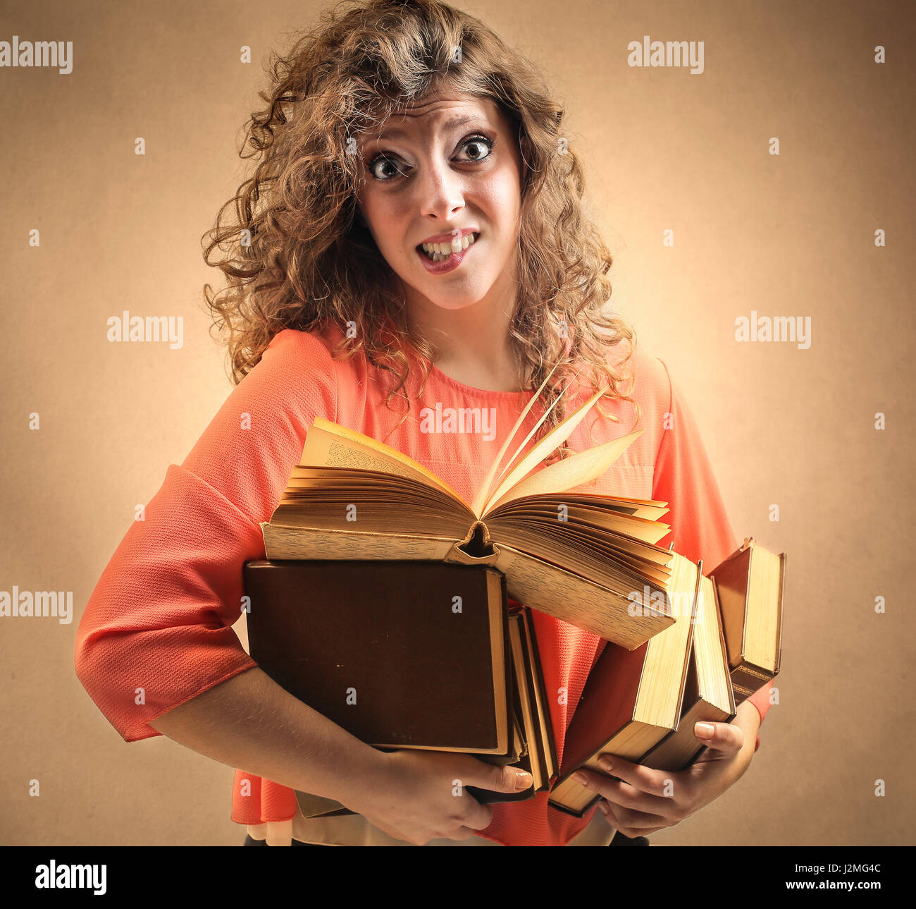 Woman carrying huge books - Stock Image