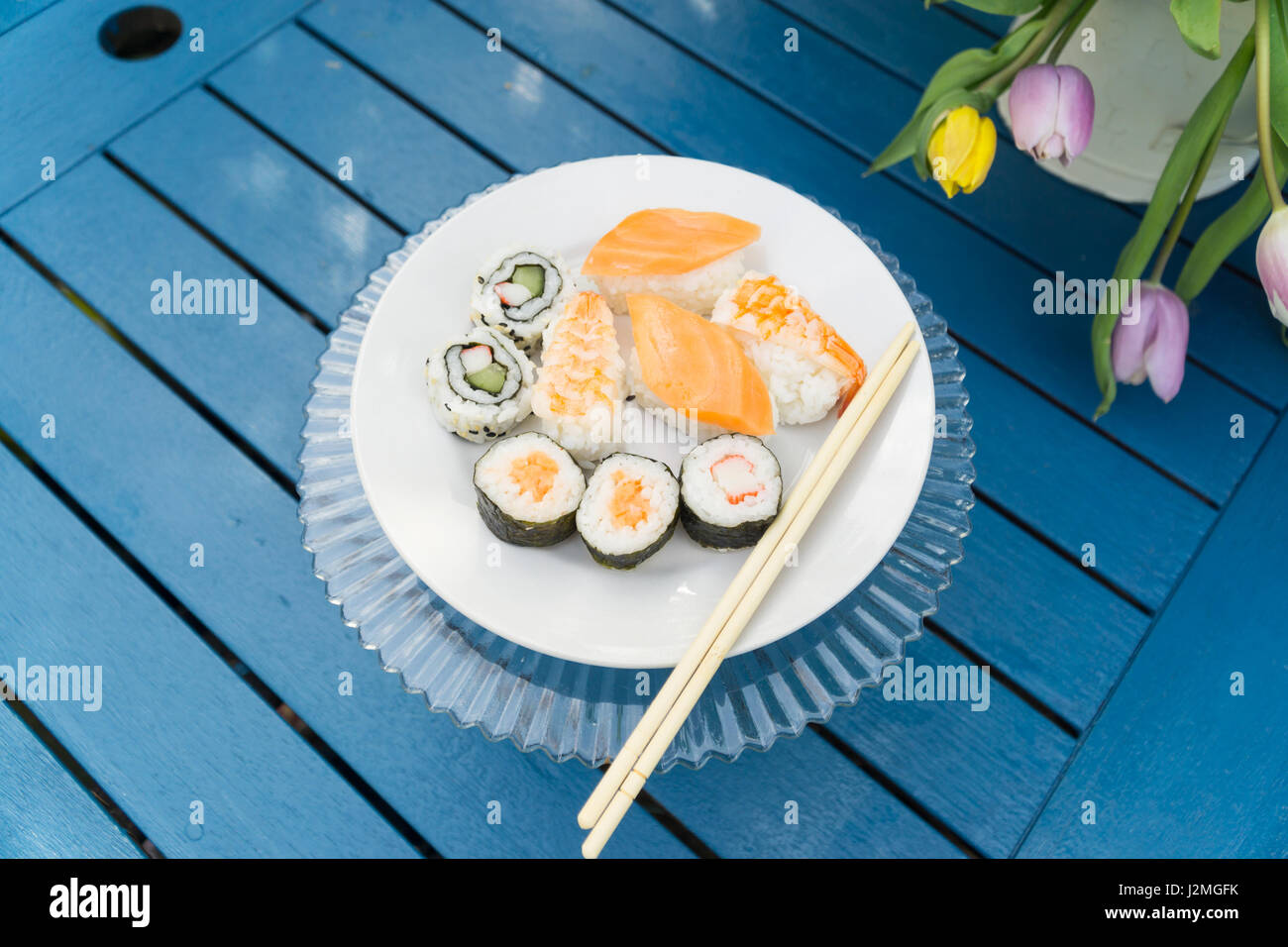 Display of sushi on a plate on a blue table in a garden with daffodils in a can - Stock Image