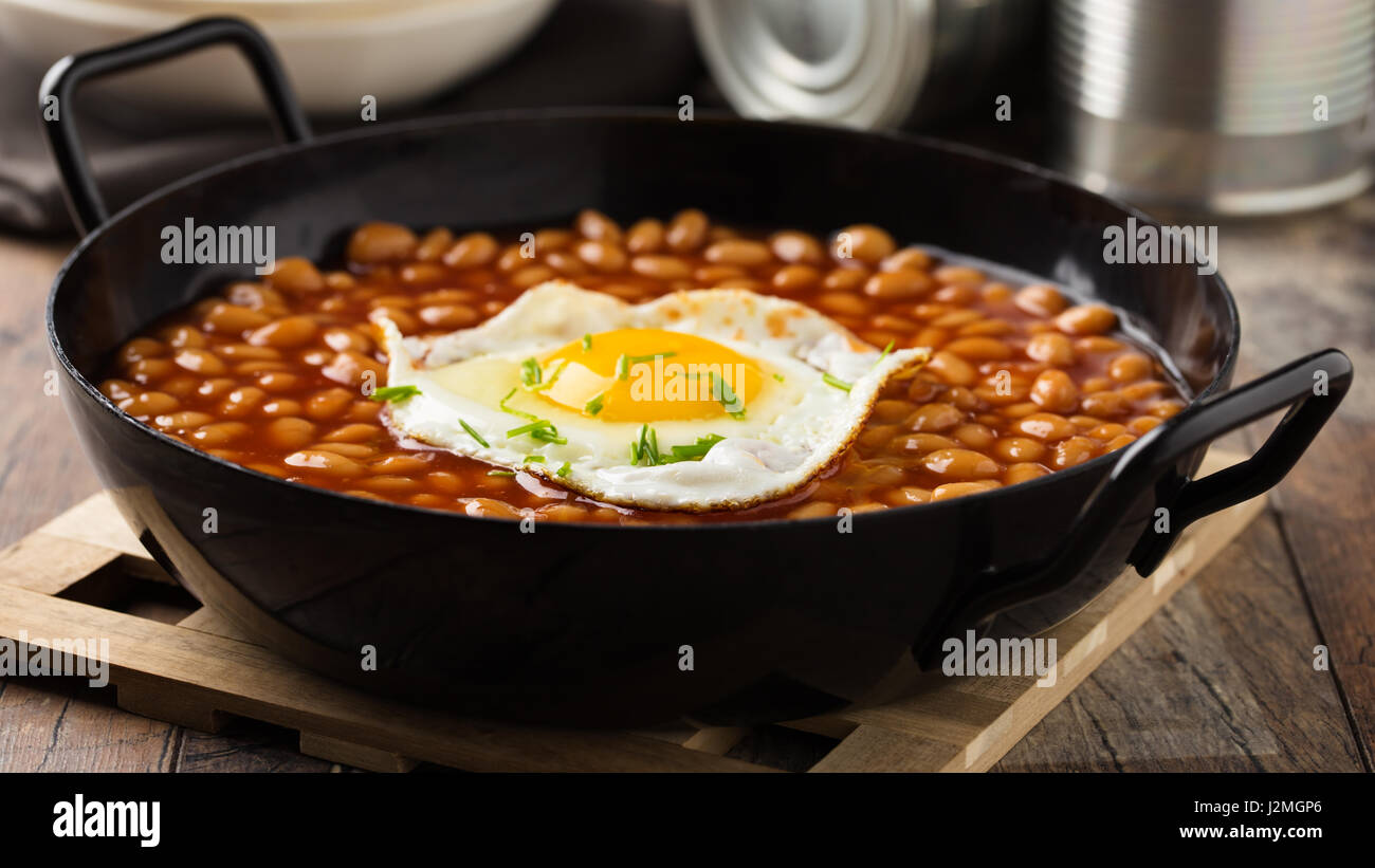 Baked beans with fried egg served in a pan. - Stock Image