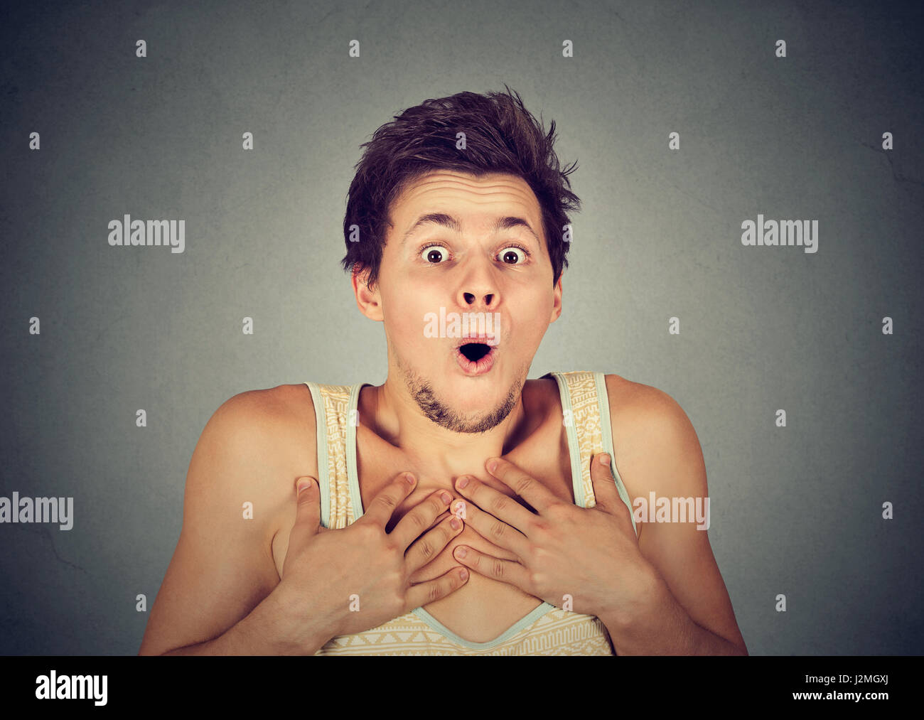 shocked surprised young man in full disbelief with hands on chest - Stock Image