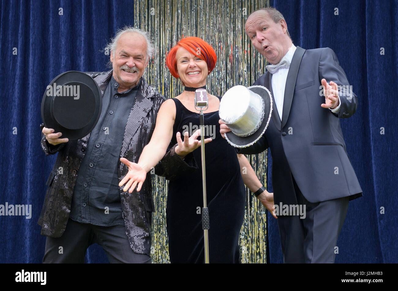 Three lively performers on stage celebrating in front of a microphone with a vivacious redhead woman and two gentlemen - Stock Image