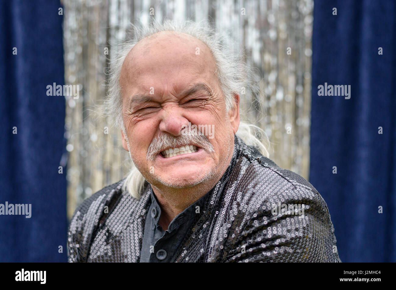 Angry balding man gnashing his teeth and grimacing in frustration in a head and shoulders portrait in front of silver - Stock Image