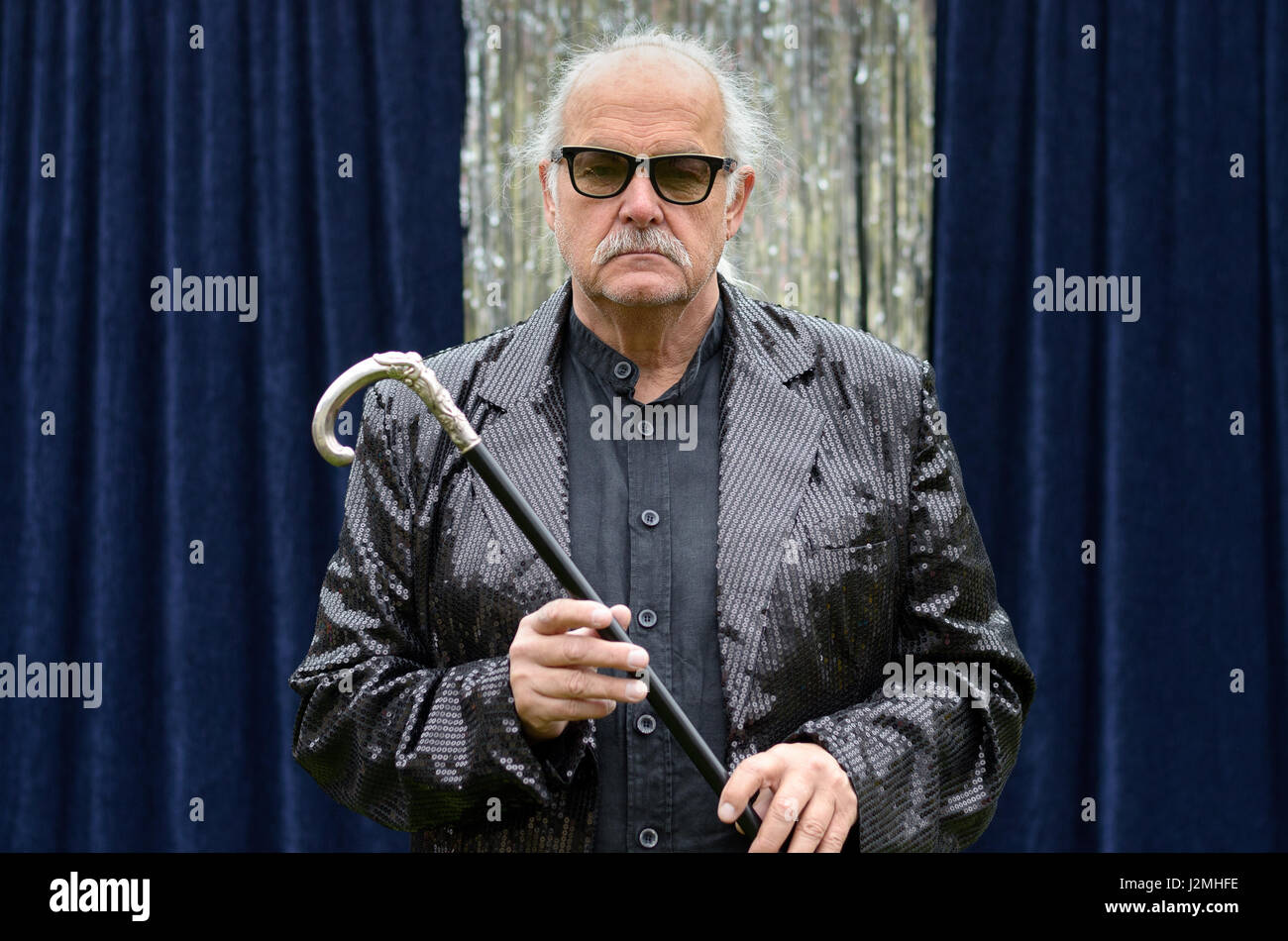 Deadpan stage performer in heavy rimmed glasses and jacket standing in front of blue curtains holding a silver topped - Stock Image
