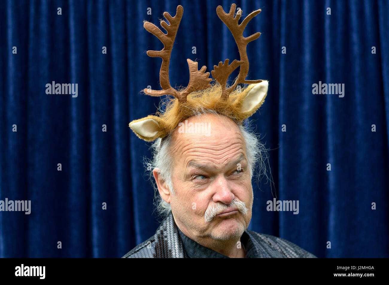 Dubious man wearing gold reindeer antlers before blue background - Stock Image