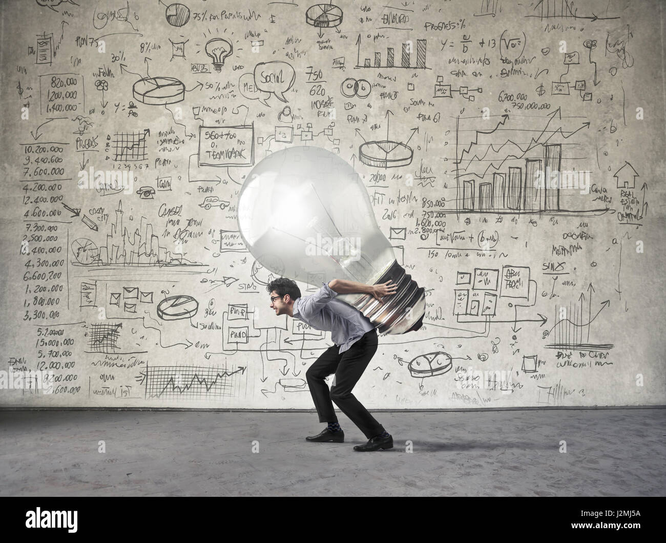 Businessman carrying lightbulb - Stock Image