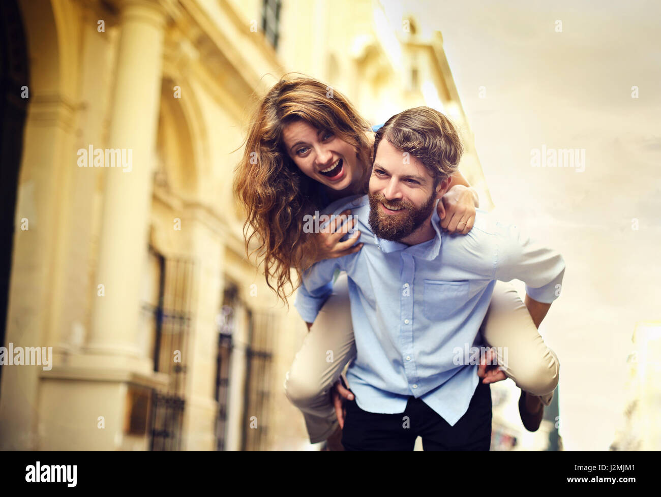 Man giving woman a piggyback - Stock Image