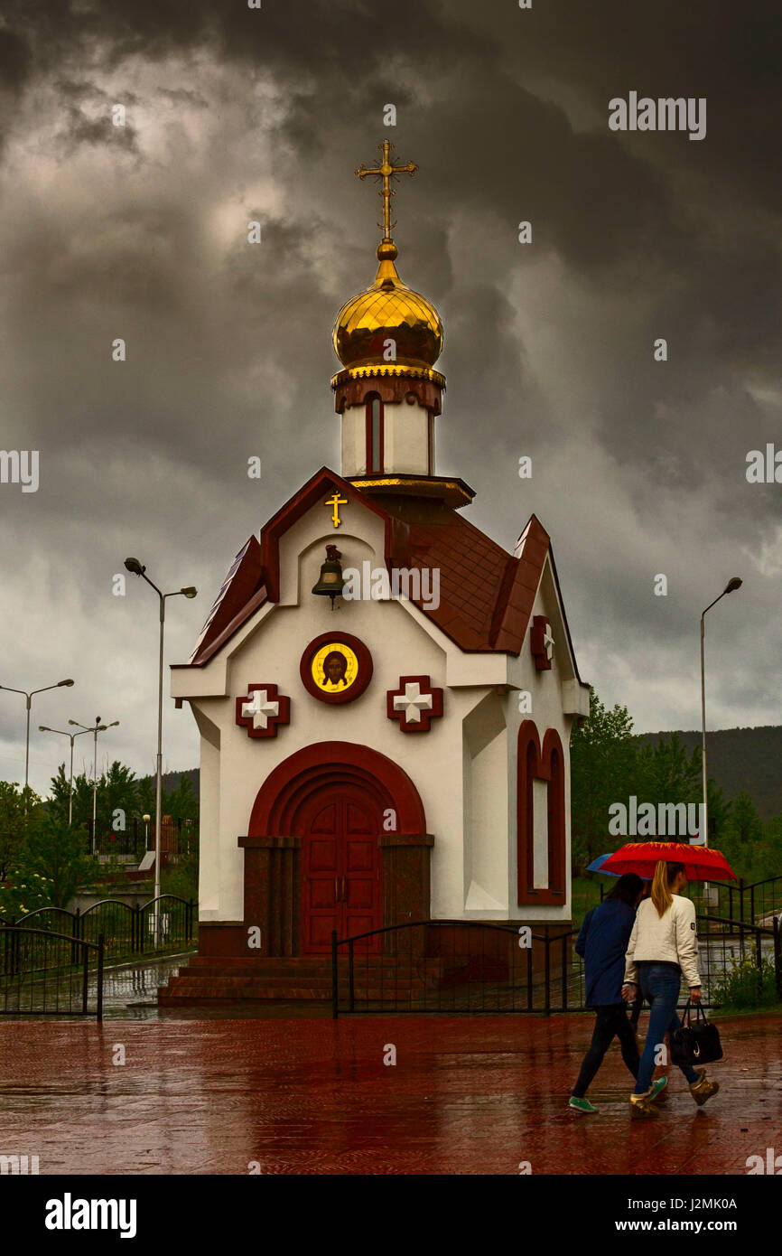 Orthodox Church against the dramatic sky on rainy day. People walk under an umbrella. - Stock Image