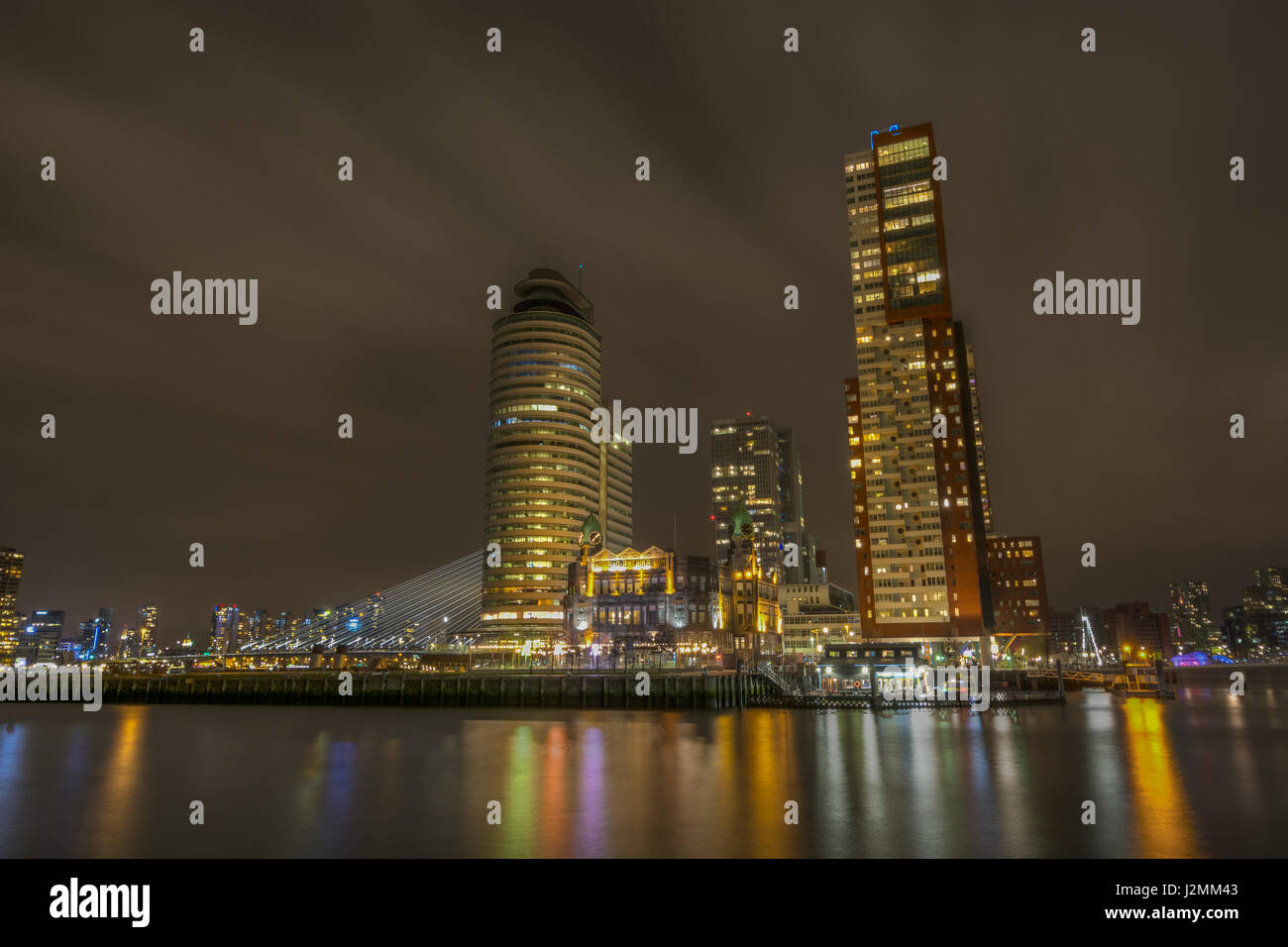The Hotel New York and Kop Van Zuid in Rotterdam, Netherlands, seen at night from Katendrecht Stock Photo