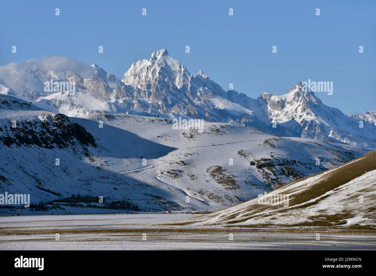 View to snow covered mountains, Grand teton Range over National Elk Refuge in winter, nice winter day, Wyoming, - Stock Image