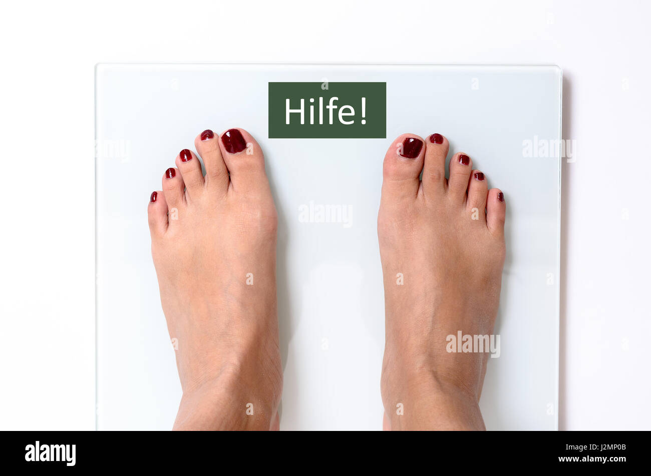 Close-up of incognito woman feet with red nail polish standing on white weight scales with word Hilfe on screen - Stock Image